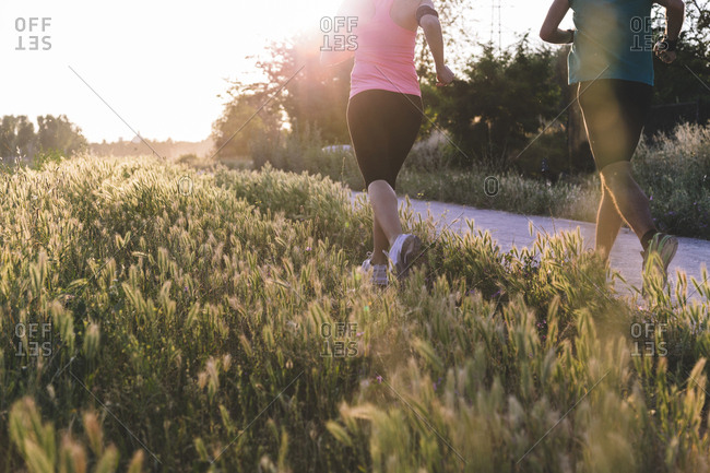 Low section of young couple jogging on field at park during sunset