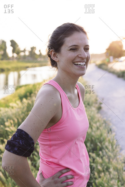 Happy sportswoman with hand on hip standing at park