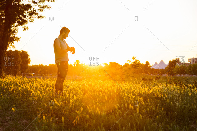 Man examining tracker while standing at grassy field against clear sky during sunset