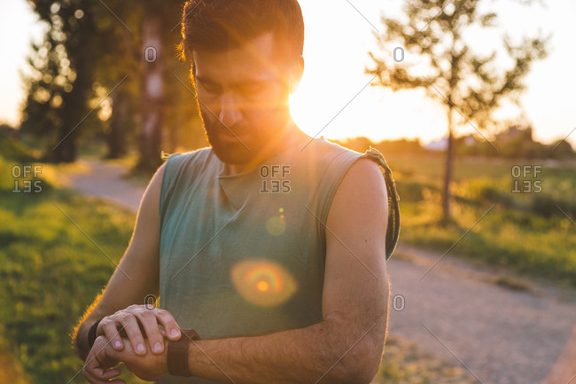 Sportsman examining wristwatch while standing at park during sunset