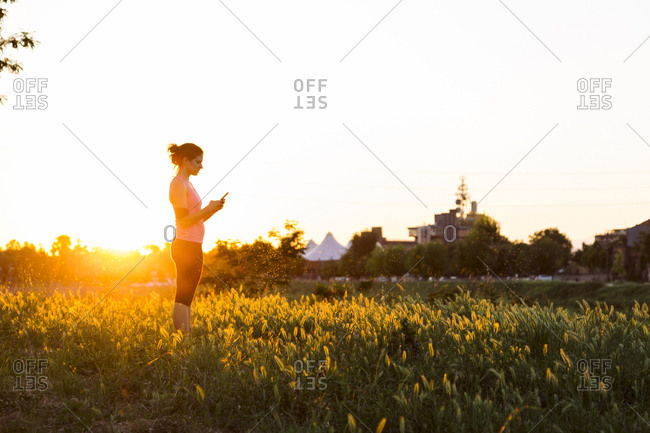 Side view of sportswoman using smart phone while standing at grassy field against clear sky during sunset