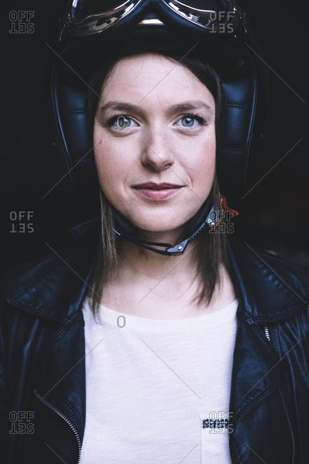 Portrait of confident female biker in workshop