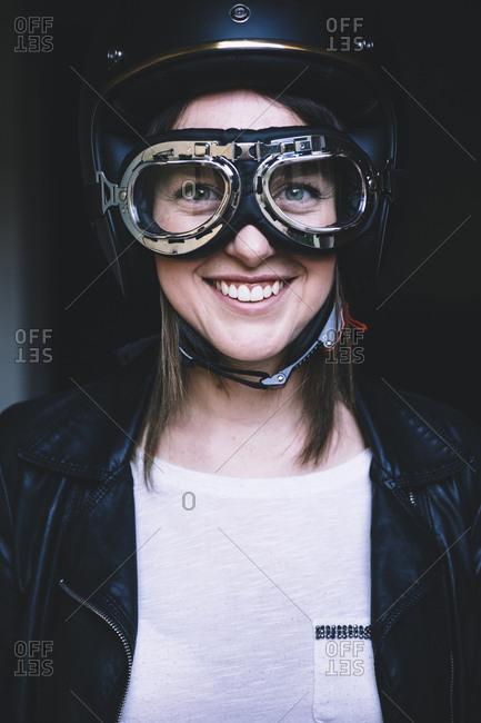 Portrait of happy female biker wearing crash helmet and flying goggles