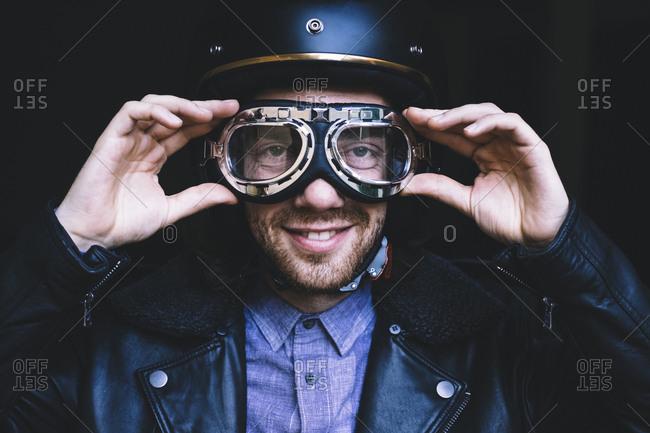 Portrait of biker adjusting flying goggles at workshop