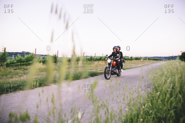 Young couple riding motorcycle on country road against clear sky