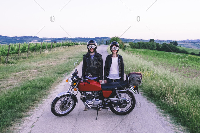 Portrait of young couple in crash helmets and flying goggles standing behind motorcycle at country road against clear sky