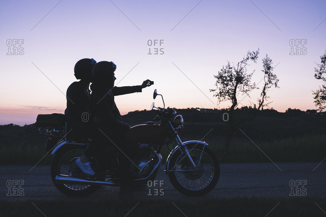 Silhouette of couple taking selfie on motorcycle at dusk