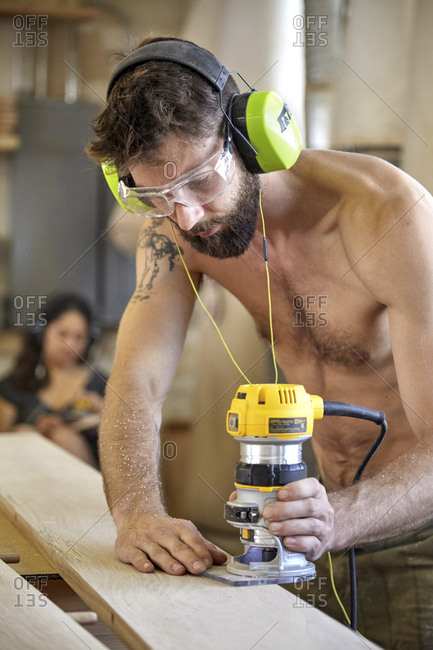 Carpenter sanding wooden plank in workshop