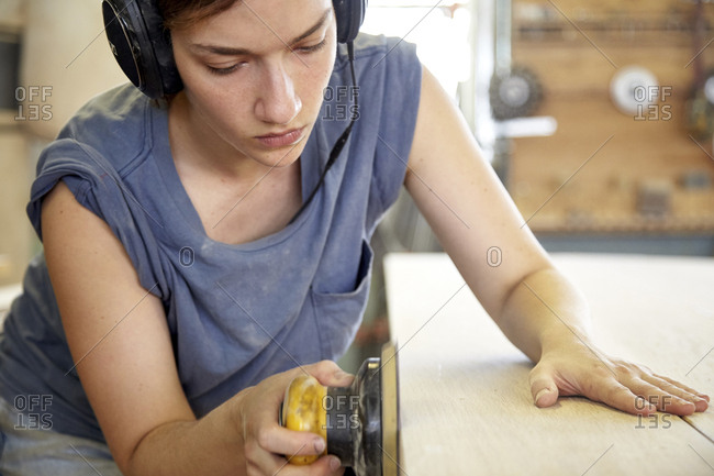 Female carpenter sanding down a table in woodshop