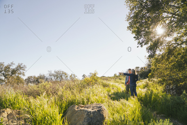 Mature woman pointing while standing by man on grassy field during sunny day