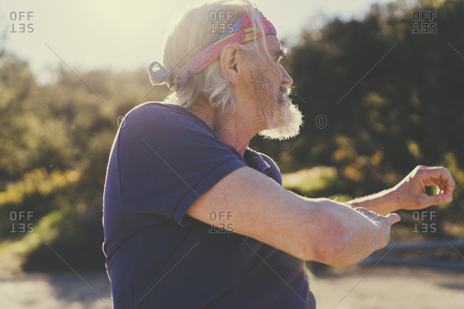 Senior man stretching while exercising on sunny day
