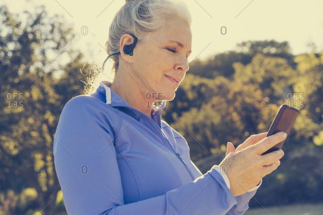 Mature woman in sportswear listening to music on earphones using smart phone