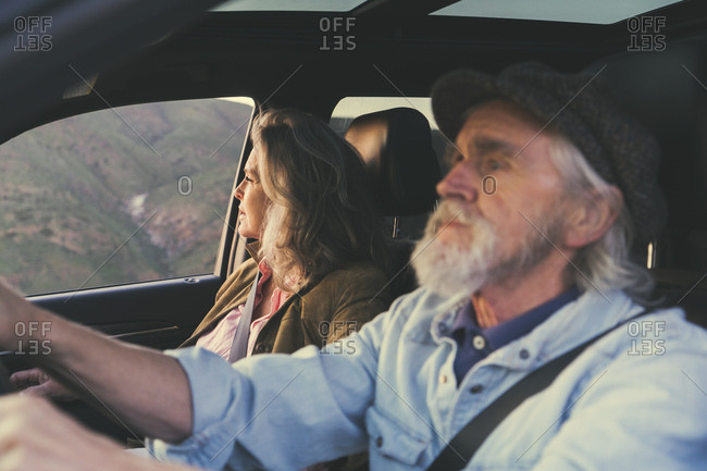Senior couple driving in car on road trip