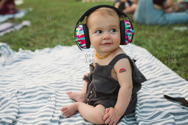 Baby on blanket with ear muffs