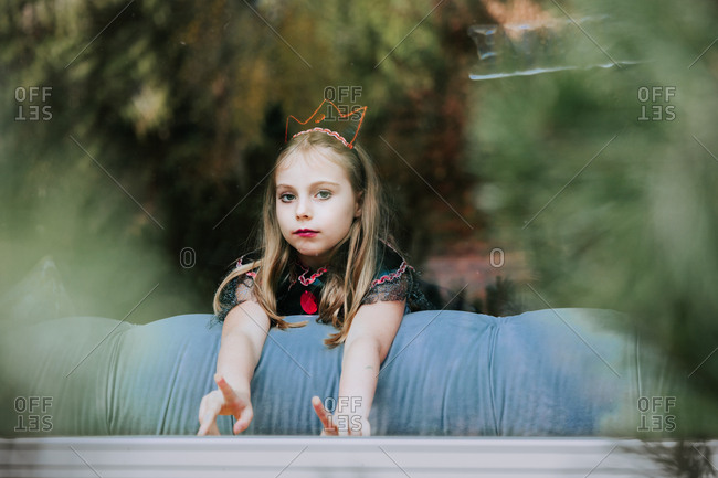 Girl in evil queen costume in window