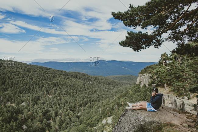 Man with headphones on mountain overlook