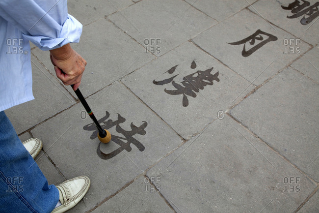 China - September 22, 2009: Person pointing to character on ground