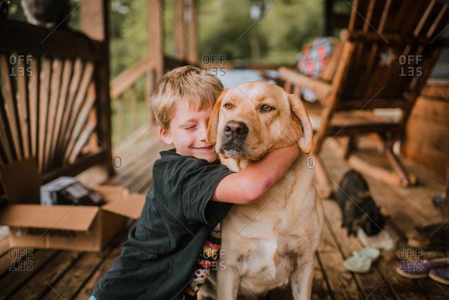 Happy boy hugging dog on porch