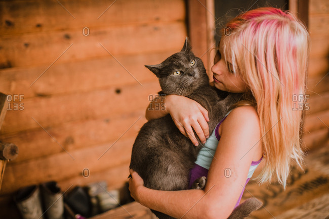 Girl with dyed hair holding cat