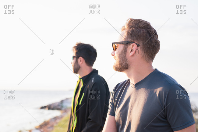 Two men wearing sunglasses looking at sunrise over water