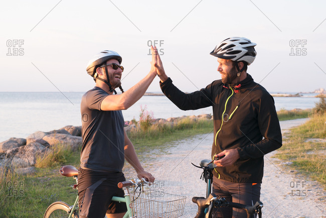 Two men high-fiving while riding bikes beside the ocean