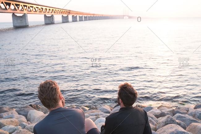Friends watching sunrise over bridge