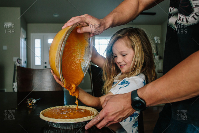 Father and son pour batter into pumpkin pie
