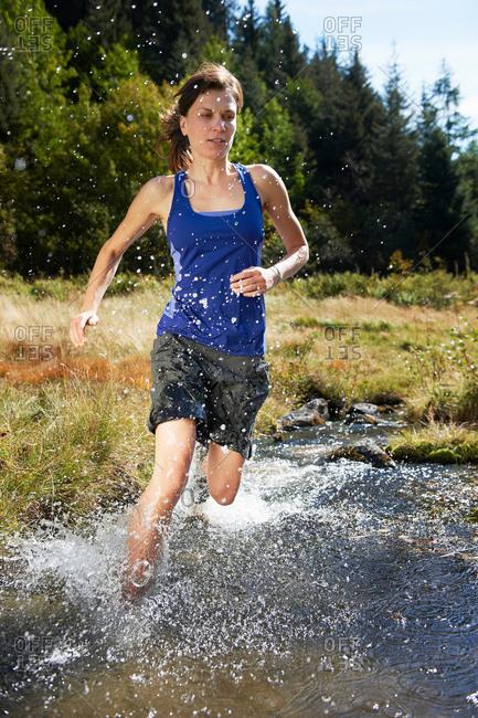 Woman running through river, Chamonix, Haute Savoie, France