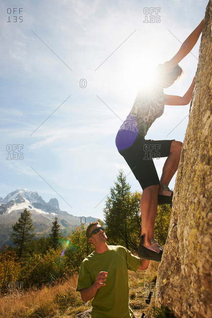 Woman rock climbing with man helping, Chamonix, Haute Savoie, France