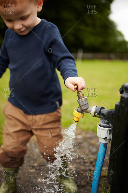 Boy playing with spout outdoors