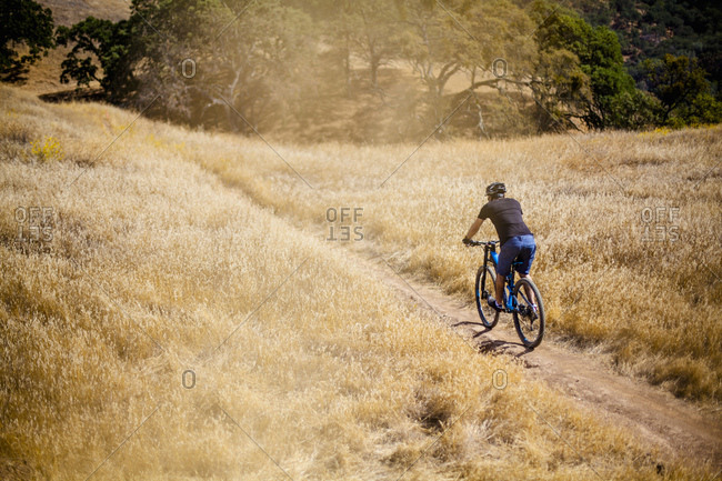 Elevated rear view of young man mountain biking on dirt track, Mount Diablo, Bay Area, California, USA