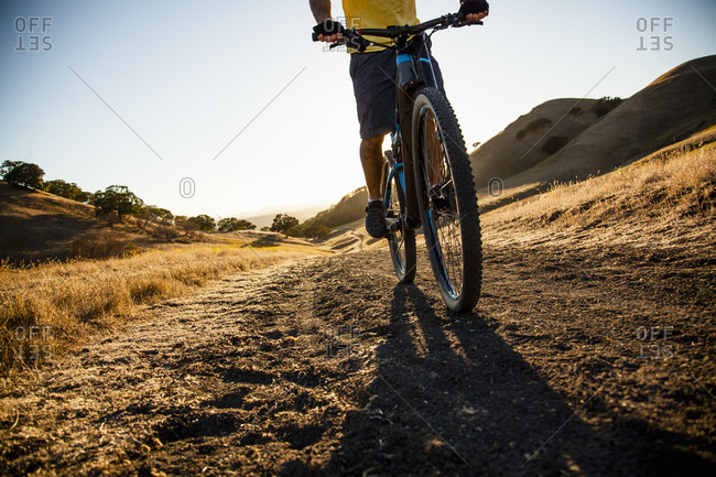 Silhouetted cropped view of young man mountain biking down dirt track, Mount Diablo, Bay Area, California, USA
