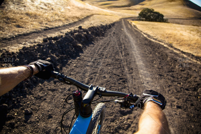 Over the shoulder view man mountain biking on dirt track, Mount Diablo, Bay Area, California, USA
