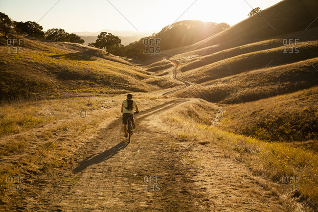 Rear view of young man mountain biking on dirt track, Mount Diablo, Bay Area, California, USA