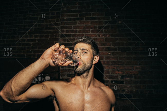 Portrait of bare chested young man drinking water on street at night