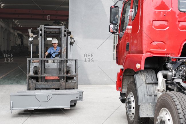 Male factory worker driving forklift truck at crane factory, China