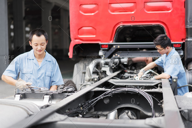 Two male factory workers teamworking on truck at crane factory, China