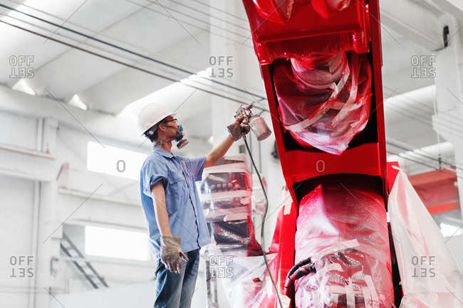 Male factory worker spray painting a red crane in factory, China