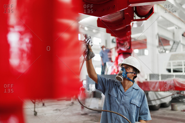 Male factory worker spray painting a red crane in factory workshop, China