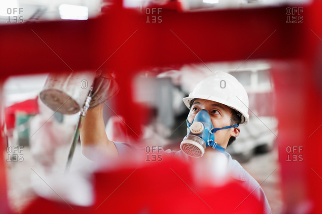 Close up of male factory worker spray painting a red crane in factory workshop, China
