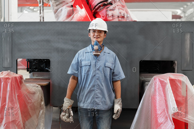 Portrait of male spray painting worker in crane factory, China