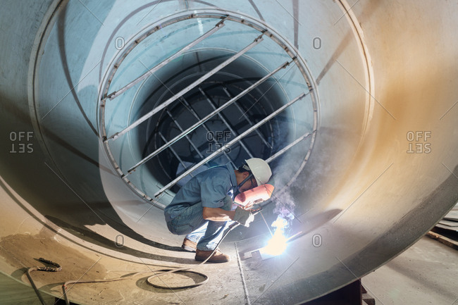 Male welder working in industrial pipe at crane factory, China