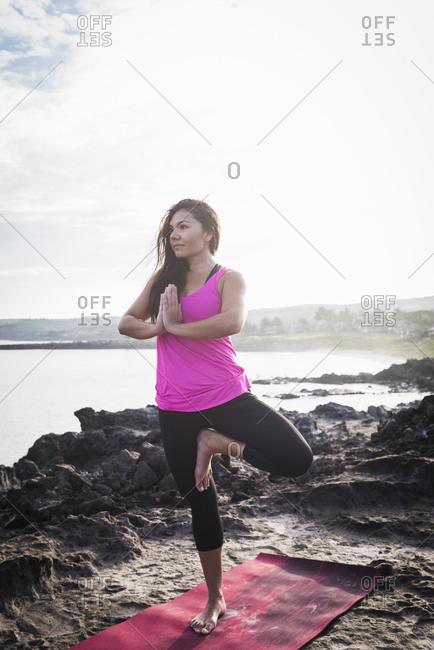 Woman at coast practicing yoga tree position, Hawea Point, Maui, Hawaii, USA