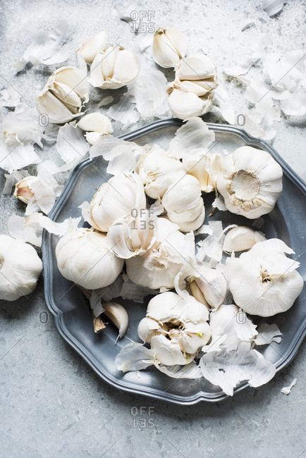 Overhead view of garlic bulbs and garlic cloves on serving dish
