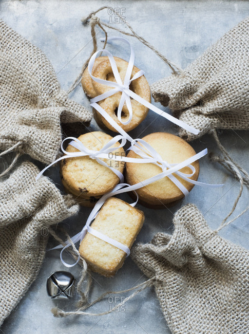 Overhead view of shortbread cookies tied with white ribbon and burlap bags