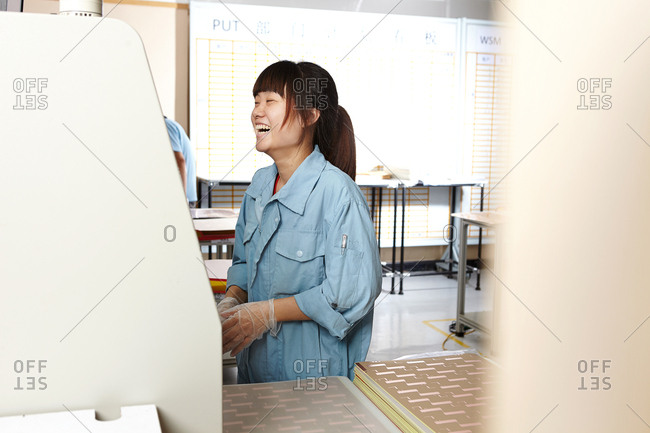 Young woman in flexible electronics plant using machine, laughing