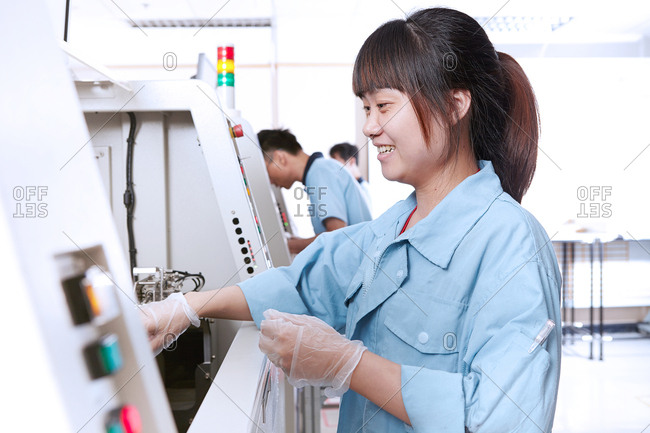 Young woman in flexible electronics plant using machine smiling