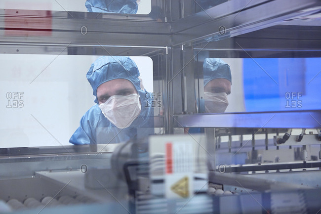 Male worker looking through machine window in flexible electronics factory clean room