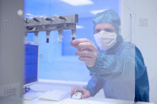 Male worker adjusting manufacturing machinery in flexible electronics factory clean room