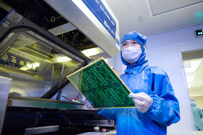 Female worker removing flex circuit from machine in flexible electronics factory clean room